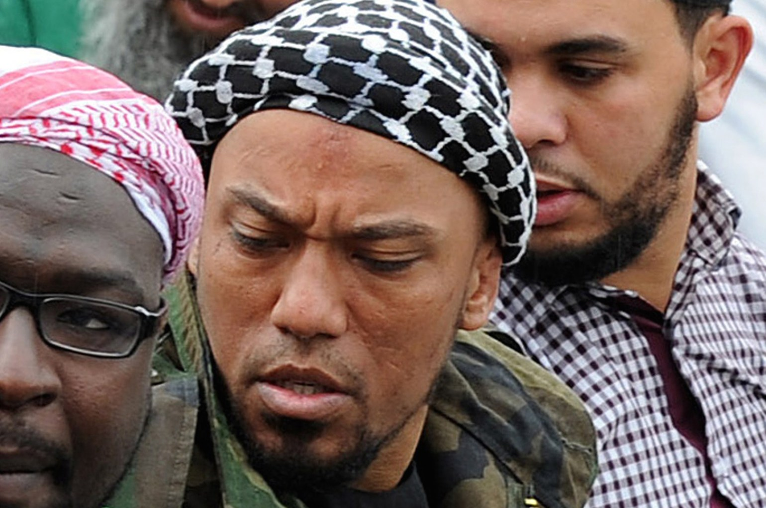 Picture taken on May 5, 2012 shows former German rapper Denis Cuspert (C) among salafi in Bonn, Germany. Denis Mamadou Cuspert, who rapped under the name Deso Dogg but took on the name Abu Talha al-Almani in Syria, was initially reported to have been killed in a suicide attack Sunday in an eastern province but hours later some retracted the claim, saying he was still alive. AFP PHOTO /DPA/ HENNING KAISER GERMANY OUT (Photo credit should read HENNING KAISER/AFP/Getty Images)