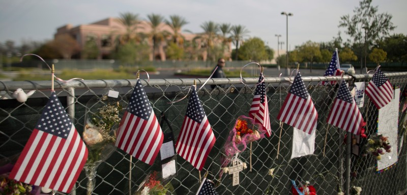 A security guard patrol sthe empty parking lot of the Inland Regional Center, site of the massacre by suspects Syed Farook and Tashfeen Malik earlier this month, near a perimeter fence covered with memorial items in San Bernardino, California, December 21, 2015. Enrique Marquez, who is alleged to have purchased the assault rifles used by the couple to kill 14 people and injure many others, appeared at a detention hearing in federal court today.   AFP PHOTO / DAVID MCNEW / AFP / DAVID MCNEW        (Photo credit should read DAVID MCNEW/AFP/Getty Images)
