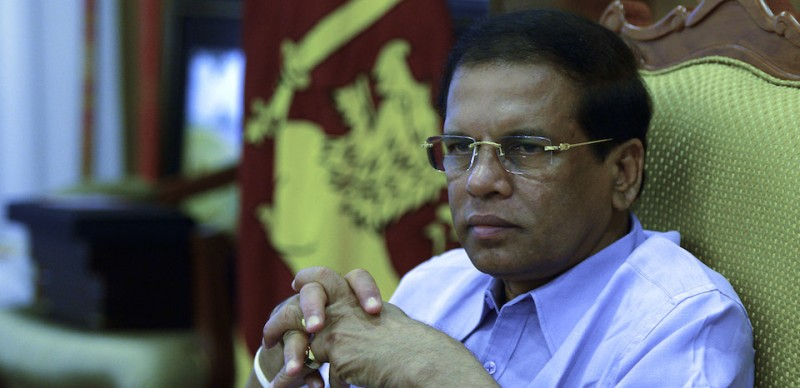 "Sri Lankan President Maithripala Sirisena listens to an AFP journalist during an interview in Colombo on January 3, 2016. Up to 100,000 people still living in camps six years after the end of Sri Lanka's ethnic war will be given land for homes within six months, President Maithripala Sirisena told AFP Sunday. ""It is an ambitious target, but I will see that all the internally displaced people are given land to build homes,"" the president said in an interview. ""I am setting up a mechanism to complete this process within six months."" AFP PHOTO / LAKRUWAN WANNIARACHCHI / AFP / LAKRUWAN WANNIARACHCHI        (Photo credit should read )"
