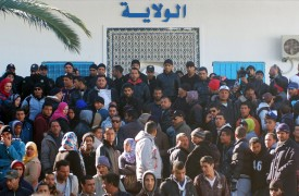 Tunisians gather outside the governorate's offices during protests after the death of an unemployed man in the central city of Kasserine on January 20, 2016.  Tunisian police fired tear gas and water cannon to disperse hundreds of job-seeking demonstrators in the impoverished town of Kasserine, in a second day of protests. The demonstrators had gathered outside the governorate's offices demanding a solution to the region's dire unemployment before heading towards the town centre, as small groups set up roadblocks with burning tyres. / AFP / MOHAMED KHALIL        (Photo credit should read MOHAMED KHALIL/AFP/Getty Images)