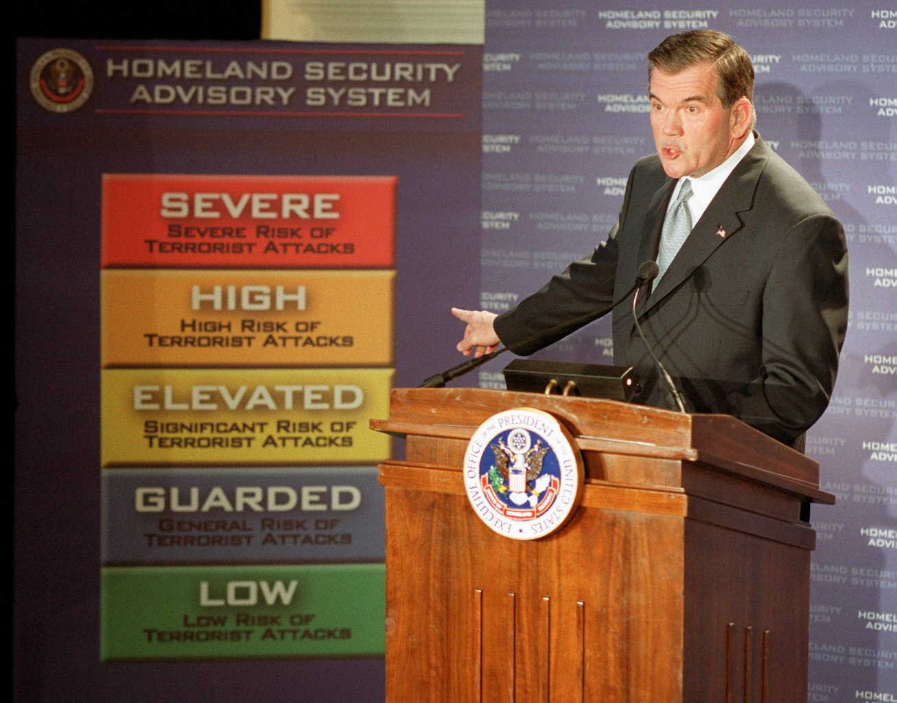 WASHINGTON, : Homeland Security Chief Tom Ridge points to a new color-coded US threat advisory system 12 March, 2002 in Washington, DC, which will allow the government and the private sector to deal effectively with threats of terrorist attack. The warning system has five levels starting with green, the lowest alert level, followed by blue, then yellow, orange and red, the highest state of alert. Each code will trigger specific actions by federal agencies and state and local governments. AFP PHOTO/JOSHUA ROBERTS (Photo credit should read JOSHUA ROBERTS/AFP/Getty Images)