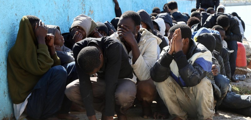 TOPSHOT - Illegal migrants sit on the dock at the Tripoli port after 115 migrants of African origins were rescued by two coast guard boats at sea when their boat started sinking off the Libyan coast on April 11, 2016.  / AFP / Mahmud TURKIA        (Photo credit should read MAHMUD TURKIA/AFP/Getty Images)