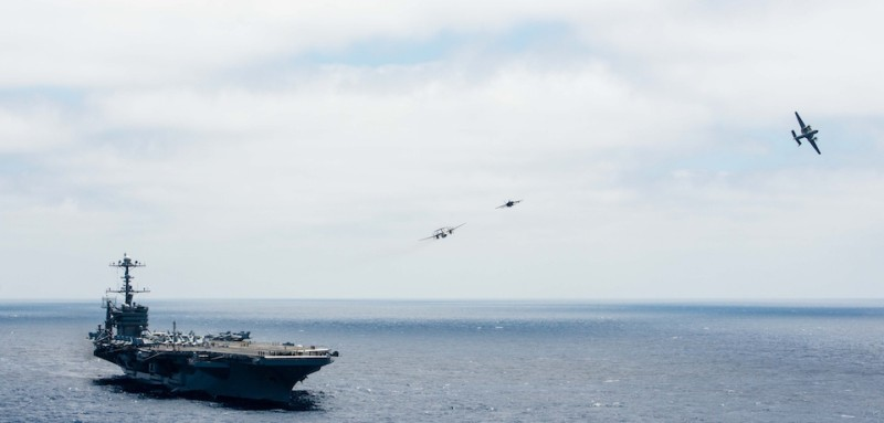 An E2-C Hawkeye piloted by Cmdr Matthew Duffy, from Kenilworth, Illinois, breaks formation turning over the Golden Hawks of Airborne Early Warning Squadron VAW 112 to Cmdr Paul Flores, from Jacksonville, Florida, during an aerial change of command ceremony above the aircraft carrier USS John C. Stennis CVN 74. Image courtesy Mass Communication Specialist 3rd Class Andre T. Richard/US Navy, 2015. (Photo by Smith Collection/Gado/Getty Images).