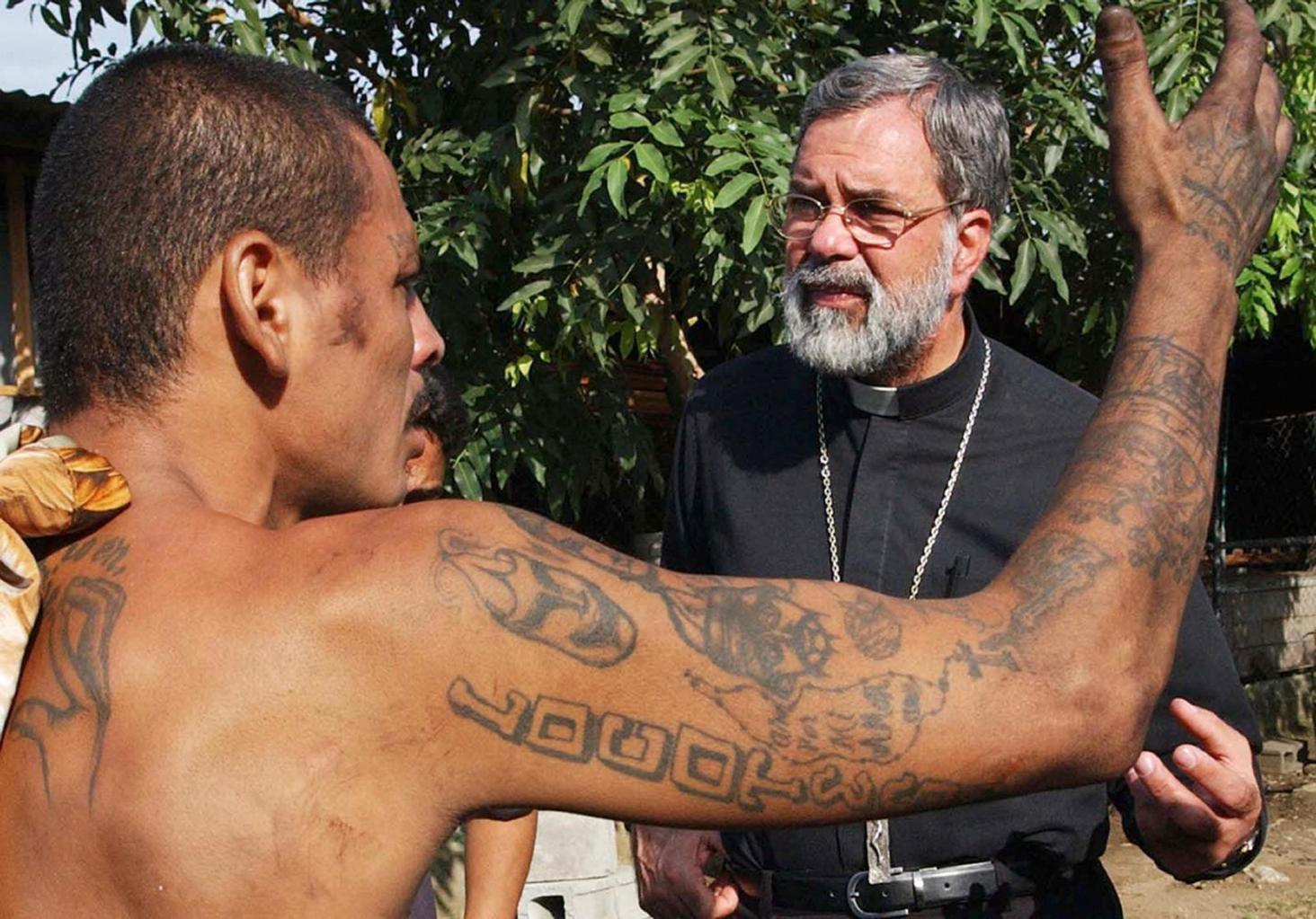 """SAN PEDRO SULA, HONDURAS: Romulo Emiliani (R), Archbishop of San Pedro Sula, speaks with a member of the Salvatrucha gang in San Pedro Sula, Honduras, 26 March 2005. Violence from street gangs, known in the region as """"maras,"""" are considered the most pressing security issues in large cities in El Salvador, Guatemala and Honduras - countries which will take part in the Anti-Maras Meeting on April 1st, in Tegucigalpa. Many of the Central American gangs have members living in the United States, and during his recent visit to Guatemala, US Defense Secretary Donald Rumsfeld announced a possible increase in US aid for the fight against terrorism, drug trafficking and gang violence in the region. AFP PHOTO/Gerardo Mazariegos (Photo credit should read GERARDO MAZARIEGOS/AFP/Getty Images)"""