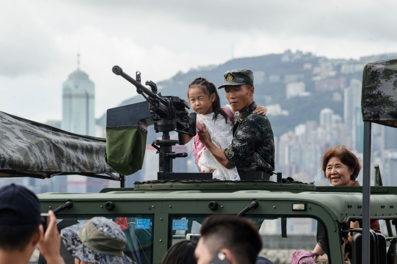 TOPSHOT - An elderly lady (R) watches as her young relative (C) is held by a PLA soldier as she looks through the iron sight of a gun during the open day of the Chinese People's Liberation Army (PLA) Navy Base at Stonecutter Island in Hong Kong on July 1, 2016, to mark the 19th anniversary of the Hong Kong handover to China . / AFP / Anthony Wallace        (Photo credit should read ANTHONY WALLACE/AFP/Getty Images)