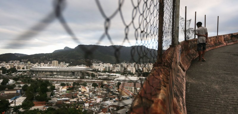 RIO DE JANEIRO, BRAZIL - JULY 7:  A teen walksl, with Maracana stadium in the background, in the Mangueira 'favela' community on July 7, 2016 in Rio de Janeiro, Brazil. Much of the Mangueira favela community sits about a kilometer away from Maracana stadium, which will be the site of the opening and closing ceremonies for the Rio 2016 Olympic Games. The stadium has received hundreds of millions of dollars in renovations ahead of the World Cup and Olympics. The Morar Carioca plan to urbanize Rio's favelas, or unplanned settlements, by 2020, was one key social legacy project heralded ahead of the Rio 2016 Olympic Games. The plan has mostly failed to materialize. Around 1.4 million residents, or approximately 22 percent of Rio's population, reside in favelas which often lack proper sanitation, health care, education and security due to gang and police violence.  (Photo by Mario Tama/Getty Images)