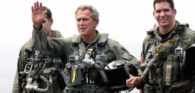 """USS ABRAHAM LINCOLN, AT SEA:  (FILES) This 01 May 2003 file photo shows US President George W. Bush (C) waving after landing in a US Navy S-3B Viking jet piloted by Commander John Lussier (R) on the USS Abraham Lincoln as the aircraft carrier sails for Naval Air Station North Island, San Diego, California. Three years after his famous photo-op before a banner hailing """"Mission Accomplished"""" in Iraq, US President George W. Bush on 01 May 2006 declared that the war-torn country had finally turned a corner in establishing security and democracy.  AFP PHOTO/Stephen JAFFE  (Photo credit should read STEPHEN JAFFE/AFP/Getty Images)"""