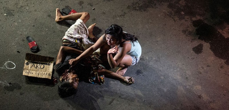 "This photo taken on July 23, 2016 shows Jennilyn Olayres grieving beside the dead body of her partner Michael Siaron who was shot by unidentified gunman and left with a cardboard sign with a message ""I'm a pusher"" along a street in Manila. Hundreds of people have died since President Rodrigo Duterte won a landslide election in May, promising to rid society of drugs and crime in six months by killing tens of thousands of criminals. Police figures showed this week that 402 drug suspects had been killed a month into Duterte's presidency. This figure does not include those slain by suspected vigilantes. / AFP / NOEL CELIS / TO GO WITH Philippines-crime-drugs-rights,FOCUS by Noel Celis        (Photo credit should read )"