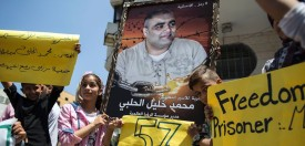Palestinian children hold posters of Mohammed Halabi (C), the Gaza director of World Vision, a major US-based Christian NGO, during a protest to support him in Gaza City on August 7, 2016. Israel charged Halabi with having diverted millions of dollars in foreign aid to the Palestinian Islamic movement Hamas and its armed wing. The Shin Bet internal security service said $7.2 million (6.5 million euros) given to World Vision had been diverted to Hamas each year, with some of it funding the Gaza Strip rulers' military campaign against Israel. / AFP / MAHMUD HAMS        (Photo credit should read )