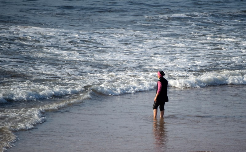 "A Moroccan woman wearing a ""burkini"", a full-body swimsuit designed for Muslim women, enters the sea at Oued Charrat beach, near the capital Rabat, on August 17, 2016. / AFP / FADEL SENNA        (Photo credit should read FADEL SENNA/AFP/Getty Images)"