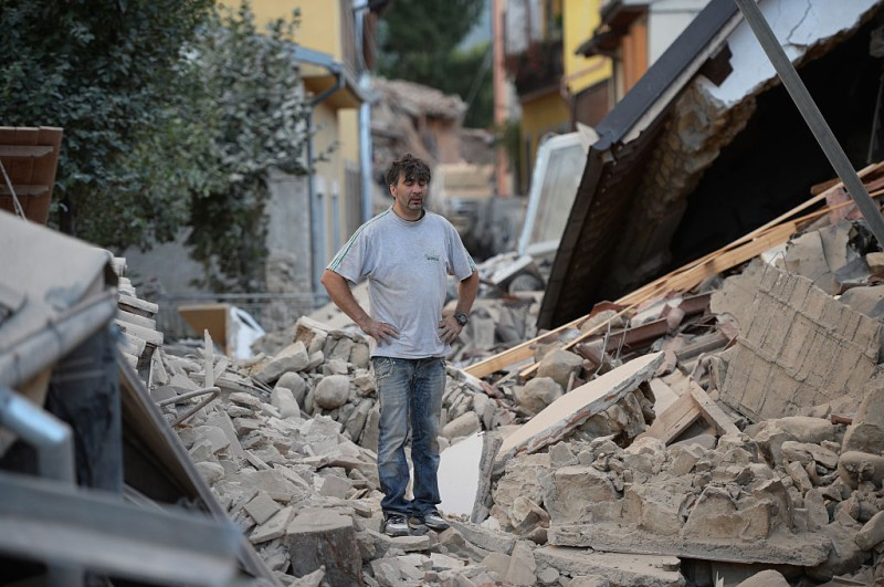 TOPSHOT - A man stands on a damaged home after a strong earthquake hit Amatrice on August 24, 2016. Central Italy was struck by a powerful, 6.2-magnitude earthquake in the early hours, which has killed at least three people and devastated dozens of mountain villages. Numerous buildings had collapsed in communities close to the epicenter of the quake near the town of Norcia in the region of Umbria, witnesses told Italian media, with an increase in the death toll highly likely. / AFP / FILIPPO MONTEFORTE        (Photo credit should read FILIPPO MONTEFORTE/AFP/Getty Images)