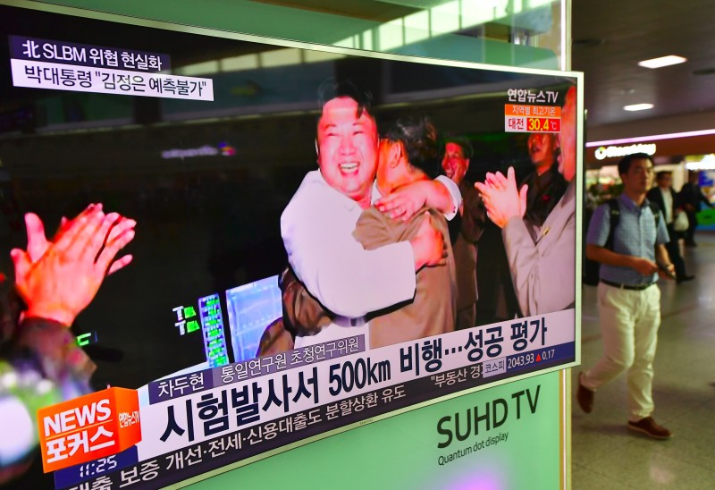 """A man walks past a television screen showing North Korean leader Kim Jong-Un celebrating its latest submarine-launched ballistic missile test at a railway station in Seoul on August 25, 2016. North Korean leader Kim Jong-Un declared a recent submarine-launched ballistic missile (SLBM) test the """"greatest success"""", Pyongyang's state media said on August 25. / AFP / JUNG YEON-JE        (Photo credit should read JUNG YEON-JE/AFP/Getty Images)"""
