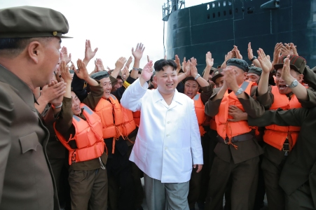 """This undated picture released from North Korea's official Korean Central News Agency (KCNA) on August 25, 2016 shows North Korean leader Kim Jong-Un (C) waving as he inspects a test-fire of strategic submarine-launched ballistic missile at an undisclosed location. / AFP / KCNA / KNS / South Korea OUT / REPUBLIC OF KOREA OUT / SOUTH KOREA OUT ---EDITORS NOTE--- RESTRICTED TO EDITORIAL USE - MANDATORY CREDIT """"AFP PHOTO/KCNA VIA KNS"""" - NO MARKETING NO ADVERTISING CAMPAIGNS - DISTRIBUTED AS A SERVICE TO CLIENTS THIS PICTURE WAS MADE AVAILABLE BY A THIRD PARTY. AFP CAN NOT INDEPENDENTLY VERIFY THE AUTHENTICITY, LOCATION, DATE AND CONTENT OF THIS IMAGE. THIS PHOTO IS DISTRIBUTED EXACTLY AS RECEIVED BY AFP. / (Photo credit should read KNS/AFP/Getty Images)"""