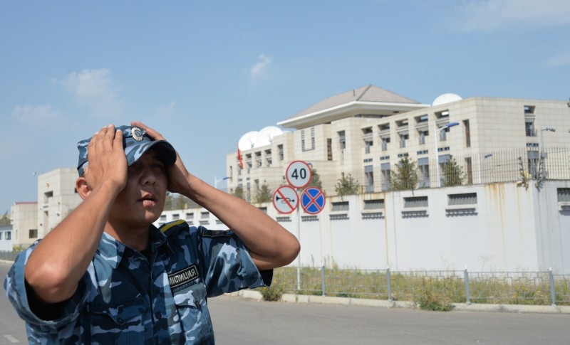 A Kyrgyz police officer patrols next to the Chinese embassy in Bishkek on August 30, 2016.  A van driven by a suicide bomber exploded after ramming through a gate at the Chinese embassy in Kyrgyzstan on August 30, wounding three people, authorities said. / AFP / Vyacheslav OSELEDKO        (Photo credit should read VYACHESLAV OSELEDKO/AFP/Getty Images)
