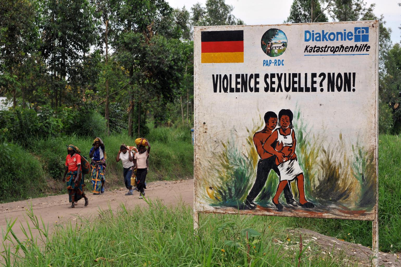 Congolese women walk past a sign opposing sexual violence on December 4, 2008 in Nyamilima, in Nord-Kivu, in the east of the Democratic Republic of Congo (DRC). There are many cases of rape and sexual vioence against women during recent fighting in this area. Months of fighting pitting Nkunda's rebels against government troops and various militia groups have displaced some 250,000 people in the eastern Congo and triggered a humanitarian crisis that has sparked international concern. AFP PHOTO / PASCAL GUYOT (Photo credit should read PASCAL GUYOT/AFP/Getty Images)