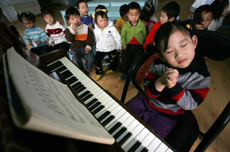 "BEIJING, CHINA:  TO GO WITH STORY ""CHINA-MUSIC-PIANO-EDUCATION"" A young girl gets ready to play the piano at the Aiyue Piano Kindergarten in Daxing on the outskirts of Beijing, 16 March 2005. Parents who put their children into the school are keen to see quick returns for their investment, and want children to learn as much and as quickly as possible.    AFP PHOTO/Peter PARKS  (Photo credit should read PETER PARKS/AFP/Getty Images)"