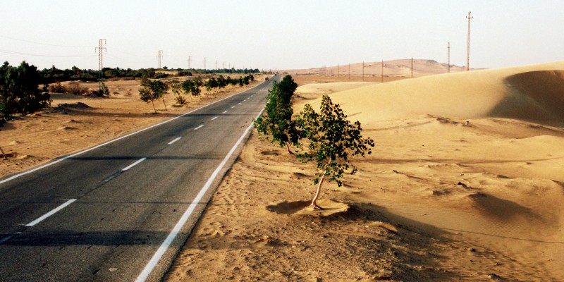 A large sand dune encroaches the main road which links surrounding villages to the nearest big town Kharga Oasis in the North.