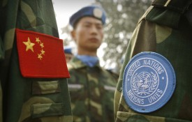 People's Liberation Army (PLA) soldiers wear the sky-blue United Nations (UN) patch signifying membership in a Chinese peacekeeping unit destined for Darfur in the Sudan along with the Chinese flag on their uniforms, at their base in China's central Henan province 15 September 2007. A 315-member engineering unit is shipping out next month in China's latest attempt to play down accusations it is worsening Darfur's agony by supporting the Khartoum regime. The unit will build bridges and roads, dig wells and perform other tasks as they showed they mean business at the military training facility.  AFP PHOTO/Peter PARKS (Photo credit should read PETER PARKS/AFP/Getty Images)