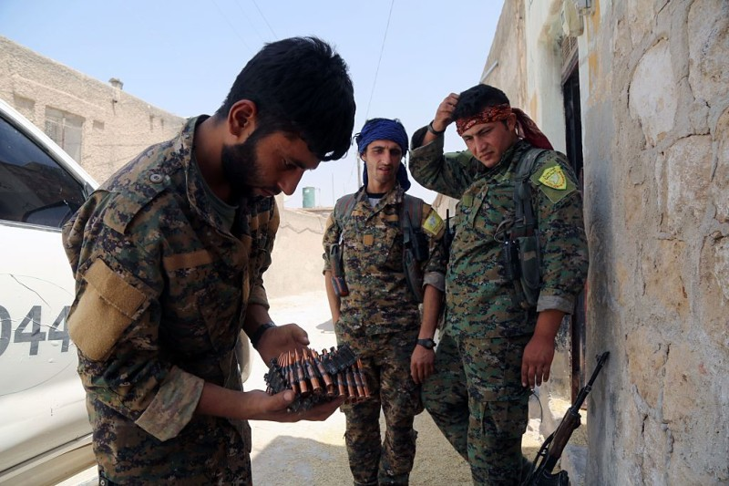 "Members of the Syrian Democratic Forces (SDF), one holding ammunition, stand on a street in the northern Syrian town of Manbij on August 7, 2016, as they comb the city in search of the last remaining jihadists, a day after they retook it from the Islamic State group. A coalition of Arab and Kurd fighters on August 6, 2016 seized the Islamic State (IS) group stronghold of Manbij, two months after launching an operation to capture the strategic city in northern Syria, a monitor said. The town had served as a key transit point along IS's supply route from the Turkish border to Raqa, the de facto capital of its self-styled Islamic ""caliphate"". / AFP / DELIL SOULEIMAN        (Photo credit should read DELIL SOULEIMAN/AFP/Getty Images)"