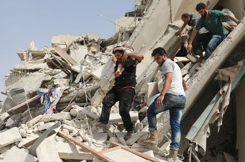Syrian men remove a baby from the rubble of a destroyed building following a reported air strike in the Qatarji neighbourhood of the northern city of Aleppo on September 21, 2016. Heavy bombardment pummelled Aleppo city and the wider province, key battlegrounds in Syria's conflict. The Syrian Observatory for Human Rights said dozens of raids hit the city's east overnight, as regime troops advanced on rebels in Aleppo's southwestern outskirts. / AFP / AMEER ALHALBI        (Photo credit should read AMEER ALHALBI/AFP/Getty Images)