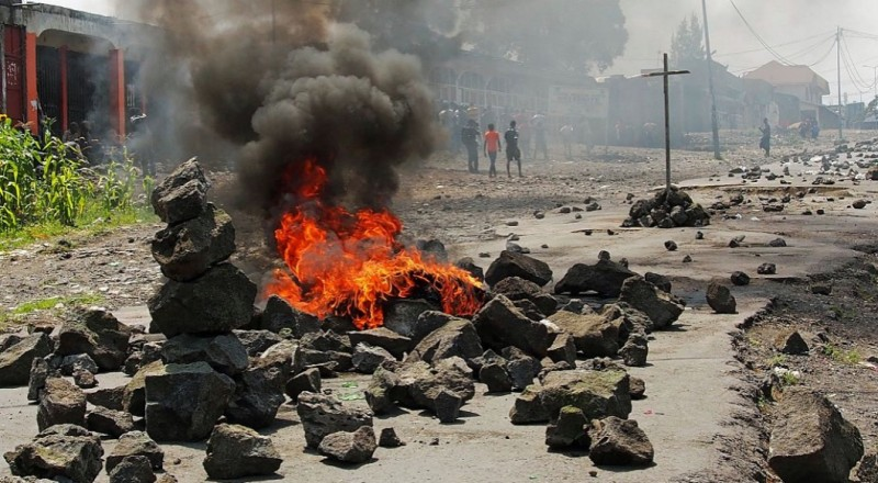 People walk past a burning barricade during a nationwide protest against long-serving President Joseph Kabila, in Goma, on May 26, 2016. Congolese security forces fired tear gas and charged at several thousand stone-throwing protesters in the capital Kinshasa Thursday as nationwide rallies against veteran President Joseph Kabila turned violent. Large numbers of riot police were deployed across the Democratic Republic of Congo for the protests called by three opposition groups in defiance of government bans. / AFP / FISTON MAHAMBA        (Photo credit should read FISTON MAHAMBA/AFP/Getty Images)