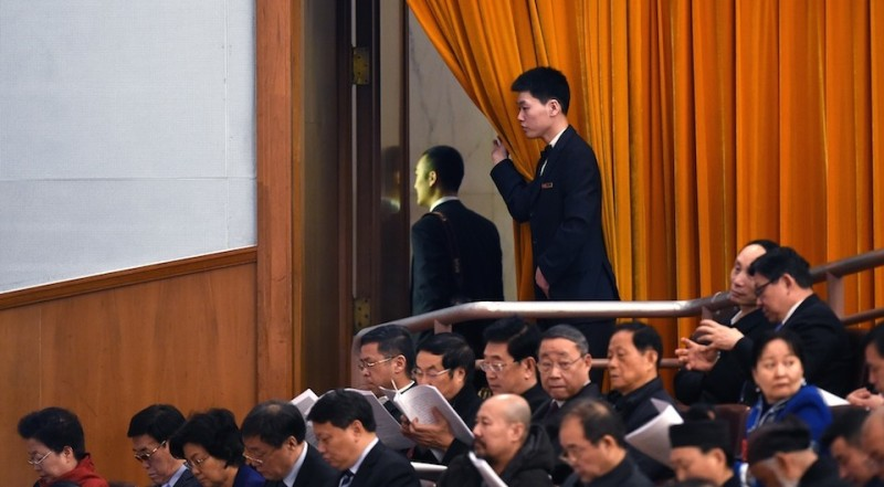 An attendant opens a curtain as a man leaves during the opening ceremony of the National People's Congress at the Great Hall of the People in Beijing on March 5, 2016. Chinas Communist-controlled parliament opened its annual session on March 5 and is expected to approve a new five-year plan to tackle slowing growth in the worlds second-largest economy.  / AFP / WANG ZHAO        (Photo credit should read WANG ZHAO/AFP/Getty Images)