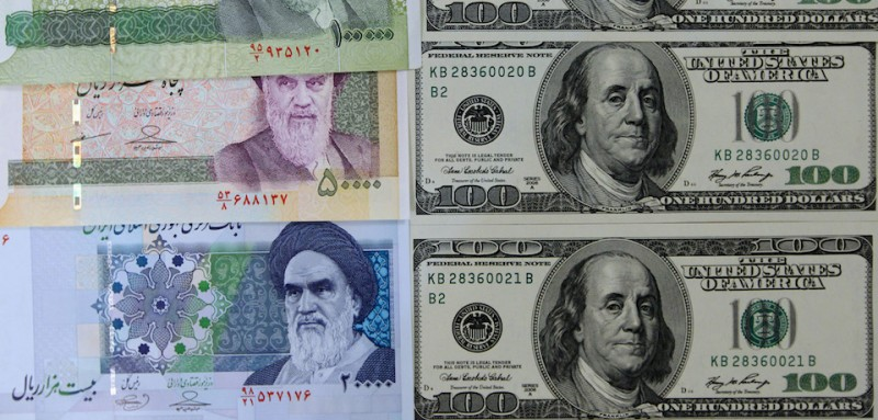 Picture taken on January 18, 2012 in Tehran shows Iran's various Rial banknotes, bearing a portrait of Iran's late founder of Islamic Republic Ayatollah Ruhollah Khomeini, next to the United States 100-dollar bills bearing the portrait of US statesman, inventor and diplomat Benjamin Franklin. The Rial's plunge, to 18,000 to the dollar hit a record low on January 18, based on rates in black market trading that the government has tried to ban. AFP PHOTO/ATTA KENARE (Photo credit should read ATTA KENARE/AFP/Getty Images)