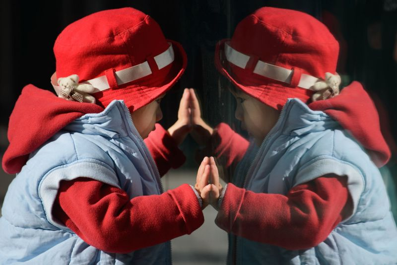 "A child looks at his reflection in a window in Beijing on November 17, 2013. On November 15 China's Communist rulers announced an easing of the country's controversial one-child policy as part of a raft of sweeping pledges including the abolition of its ""re-education"" labour camps and loosening controls on the economy. AFP PHOTO / Ed Jones        (Photo credit should read Ed Jones/AFP/Getty Images)"