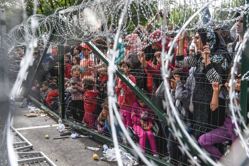 Refugees stand behind a fence at the Hungarian border with Serbia near the town of Horgos on September 16, 2015. Europe's 20-year passport-free Schengen zone appeared to be a risk of crumbling with Germany boosting border controls on parts of its frontier with France as migrants desperate to find a way around Hungary's border fence began crossing into Croatia. With a string of EU countries tightened frontier controls in the face of the unprecedented human influx, the cherished principle of free movement across borders -- a pillar of the European project -- seemed in grave jeopardy.  / AFP / ARMEND NIMANI        (Photo credit should read ARMEND NIMANI/AFP/Getty Images)
