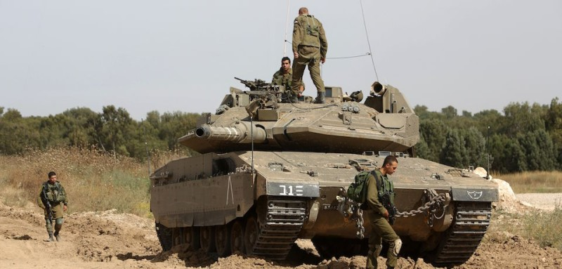 Israeli soldiers stand guard with their tank along the border between Israel and the Gaza Strip near the southern Israeli Kibbutz of Nahal Oz on May 4, 2016. The border between Israel and the Gaza Strip saw a bout of violence, with exchanges of fire that put a 2014 ceasefire agreement to the test. Israeli tanks fired into the Hamas-run Palestinian enclave at least twice, saying it was in response to mortar fire across the border, while the army designated an Israeli border town a closed military zone.   / AFP / MENAHEM KAHANA        (Photo credit should read MENAHEM KAHANA/AFP/Getty Images)