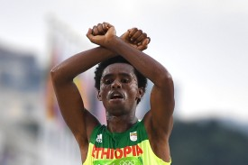 Ethiopia's Feyisa Lilesa crossed his arms above his head at the finish line of the Men's Marathon athletics event of the Rio 2016 Olympic Games at the Sambodromo in Rio de Janeiro on August 21, 2016.   Lilesa crossed his arms above his head as he finished the race as a protest against the Ethiopian government's crackdown on political dissent.  / AFP / OLIVIER MORIN        (Photo credit should read OLIVIER MORIN/AFP/Getty Images)