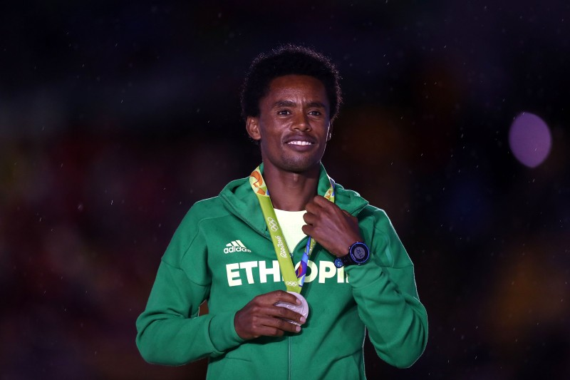 RIO DE JANEIRO, BRAZIL - AUGUST 21:  Silver medalist Feyisa Lilesa of Ethiopia stands on the podium during the medal ceremony for the Men's Marathon during the Closing Ceremony on Day 16 of the Rio 2016 Olympic Games at Maracana Stadium on August 21, 2016 in Rio de Janeiro, Brazil.  (Photo by Ezra Shaw/Getty Images)