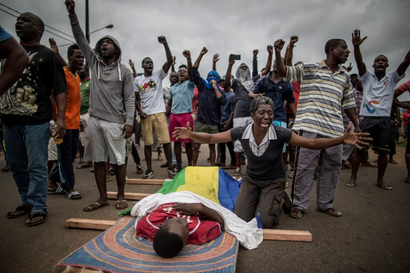 TOPSHOT - A woman cries over the body of Axel Messa, 30, wrapped in the flag of Gabon as he is laying on the ground, prior to a funeral procession, in a street of the Libreville district of Nzeng Ayong on September 2, 2016. His mother told AFP he was shot in front of his home on September 1, 2016 night. Two men died after overnight clashes in Gabon's capital Libreville between security forces and demonstrators protesting President Ali Bongo's announced victory in a disputed election, witnesses and an AFP journalists said on September 2, 2016. The latest deaths take the toll up to five killed since riots and protests broke out on August 31, 2016 after Bongo was declared the winner of the weekend presidential vote by a razor-thin margin.  / AFP / MARCO LONGARI        (Photo credit should read MARCO LONGARI/AFP/Getty Images)