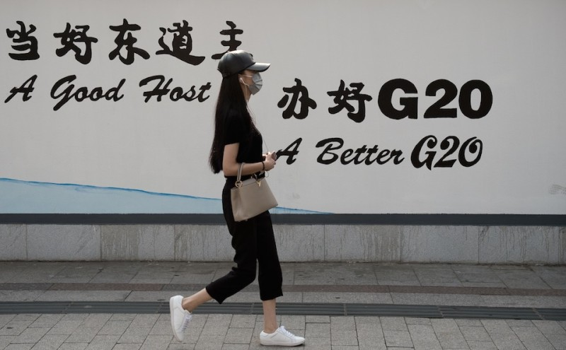 A young woman walks in a street in Hangzhou on September 2, 2016. Factories have been closed to ensure blue skies, potential troublemakers detained and a quarter of the residents have left: welcome to Hangzhou, a city China's ruling Communist Party is determined will look its best for the G20 summit. / AFP / NICOLAS ASFOURI / TO GO WITH AFP STORY: China-G20-diplomacy , Focus by Tom HANCOCK         (Photo credit should read NICOLAS ASFOURI/AFP/Getty Images)