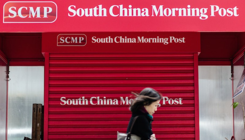 A pedestrian walks past a closed newsstand designed with the logo of the South China Morning Post (SCMP) in Hong Kong on December 12, 2015, following its acquisition by Chinese internet giant Alibaba of the English-language newspaper. Alibaba said on December 11 it would buy Hong Kong's South China Morning Post, pledging to maintain the newspaper's objectivity in the face of fears it will lose its independent voice.   AFP PHOTO / ANTHONY WALLACE / AFP / ANTHONY WALLACE        (Photo credit should read ANTHONY WALLACE/AFP/Getty Images)