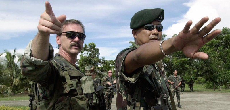 CARMEN, PHILIPPINES:  US Army Special Forces 1st Sgt Gordon Waugh (L) and Captain Miguel Ceballos (R) of the Philippine army give instruction to their men during  a Force protection and Security training as part of a joint counter-terrorist exercise held at the Philippine Army training base at Camp Lucero in Carmen on the southern island of Mindanao, 29 July 2004. The US mllitary advisers will train Filipino troops to fight al-Qaeda-linked Muslim militants in Mindanao.    AFP PHOTO Joel NITO  (Photo credit should read JOEL NITO/AFP/Getty Images)