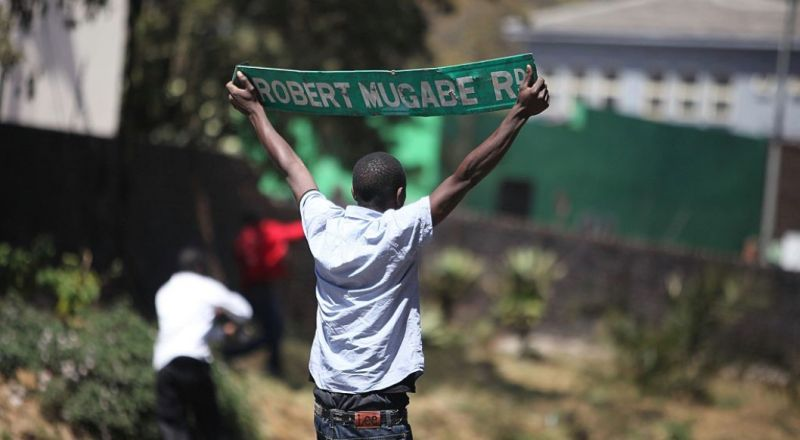 "A protester holds up a street sign with President Robert Mugabe name on it as Zimbabwe opposition supporters clash with police during a protest march for electoral reforms on August 26, 2016 in Harare. Riots erupted in Zimbabwe's capital Harare after police fired tear gas and beat protesters who responded by throwing stones in the latest of a string of tense demonstrations.  The violence came a day after a High Court judge had ordered police ""not to interfere (with), obstruct or stop the march"". Dozens of police blocked off the site of an opposition rally to demand electoral reforms before 2018 when 92-year-old President Robert Mugabe, who has ruled the southern African country for decades, will seek re-election. / AFP / WILFRED KAJESE        (Photo credit should read WILFRED KAJESE/AFP/Getty Images)"