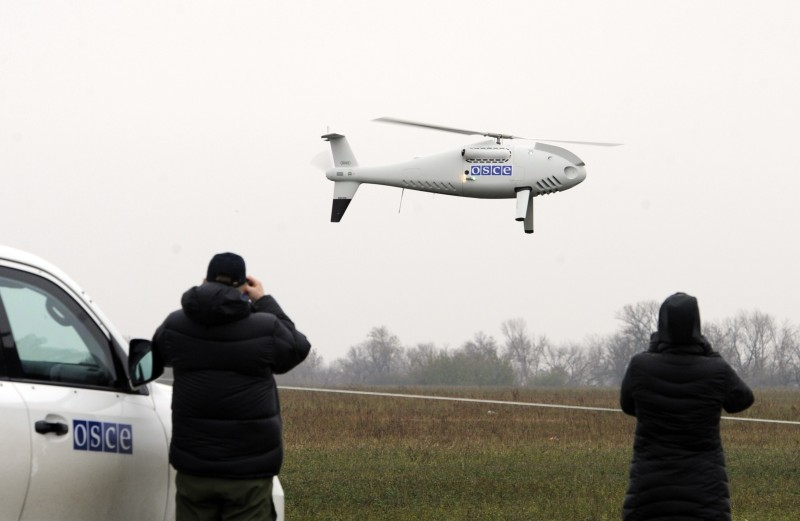 People watch on October 23, 2014 an unarmed/unmanned aerial vehicle (UAV) during a test flight near the southeastern Ukrainian city of Mariupol. The Organization for Security and Cooperation in Europe (OSCE) Special Monitoring Mission to Ukraine (SMM) on October 23 successfully completed the maiden flight of its UAVs. Four drones will be deployed on October 24 to monitor the peace deal reached last month in the Belarussian capital Minsk between Kiev, Moscow and the pro-Russian separatists in east Ukraine. The accord includes OSCE monitoring and verification on both sides of the border.    AFP PHOTO/ ALEXANDER KHUDOTEPLY        (Photo credit should read Alexander KHUDOTEPLY/AFP/Getty Images)