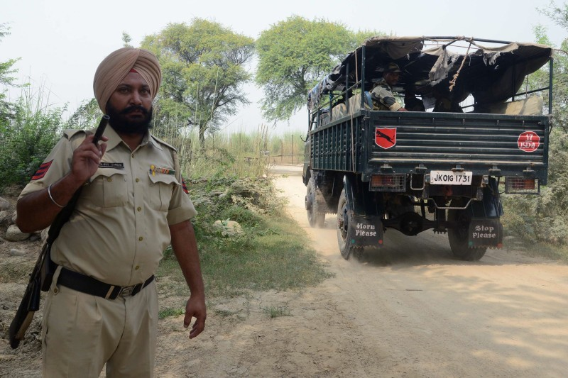 An Indian Punjab policeman stands guard as Border Security Force (BSF) personnel sit in a vehicle near the Indian-Pakistan border at Rear Kakkar, about 40km from Amritsar, on October 4, 2016. / AFP / NARINDER NANU        (Photo credit should read NARINDER NANU/AFP/Getty Images)