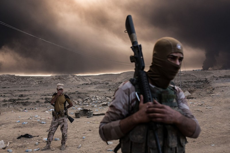 TOPSHOT - Iraqi soldiers look on as smoke rises from the Qayyarah area, some 60 kilometres (35 miles) south of Mosul, on October 19, 2016, as Iraqi forces take part in an operation against Islamic State (IS) group jihadists to retake the main hub city. In the biggest Iraqi military operation in years, forces have retaken dozens of villages, mostly south and east of Mosul, and are planning multiple assaults for October 20. / AFP / YASIN AKGUL        (Photo credit should read YASIN AKGUL/AFP/Getty Images)