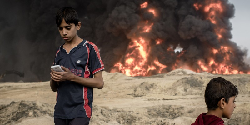 Two boys stand near a burning oil pit in Qayyarah, Iraq.