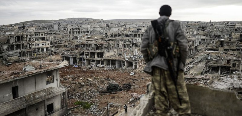 Musa, a 25-year-old Kurdish marksman, stands atop a building as he looks at the destroyed Syrian town of Kobane, also known as Ain al-Arab, on January 30, 2015. Kurdish forces recaptured the town on the Turkish frontier on January 26, in a symbolic blow to the jihadists who have seized large swathes of territory in their onslaught across Syria and Iraq.     AFP PHOTO/BULENT KILIC / AFP / BULENT KILIC AND -        (Photo credit should read BULENT KILIC/AFP/Getty Images)