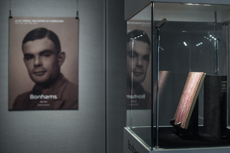 "A rare manuscript (R) belonging to British mathematician and code breaker Alan Turing (L, depicted on a poster) is displayed in Hong Kong on March 19, 2015. The handwritten notebook from the early 1940s gives an intimate insight into the ""father of the modern computer"" and was shown ahead of an auction in New York where it is expected to fetch at least one million USD.  AFP PHOTO / Philippe Lopez        (Photo credit should read PHILIPPE LOPEZ/AFP/Getty Images)"