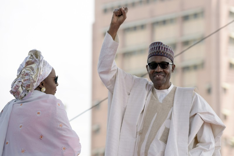 Nigerian President Mohammadu Buhari, next to his wife Aisha, raises his fist to greet the crowd before taking oath of office at the Eagles Square in Abuja, on May 29, 2015. Buhari, 72, defeated Jonathan in March 28 elections -- the first time in Nigeria's history that an opposition candidate had beaten a sitting president. AFP PHOTO/PIUS UTOMI EKPEI        (Photo credit should read PIUS UTOMI EKPEI/AFP/Getty Images)
