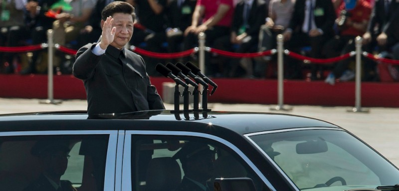 BEIJING, CHINA - SEPTEMBER 03:  Chinese president and leader of the Communist Party Xi Jinping rides in an open top car as he greets soldiers and others in front of Tiananmen Square and the Forbidden City during a military parade on September 3, 2015 in Beijing, China. China is marking the 70th anniversary of the end of World War II and its role in defeating Japan with a new national holiday and a military parade in Beijing.  (Photo by Kevin Frayer/Getty Images)