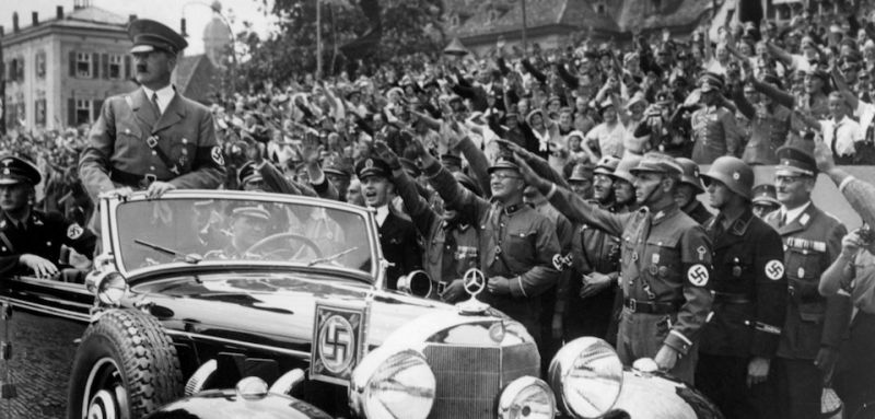 GERMANY:German Chancellor Adolf Hitler (L) standing in a convertible Mercedes reviews SA and SS troops and wellwishers in 1937 somewhere in Germany. (Photo credit should read AFP/Getty Images)