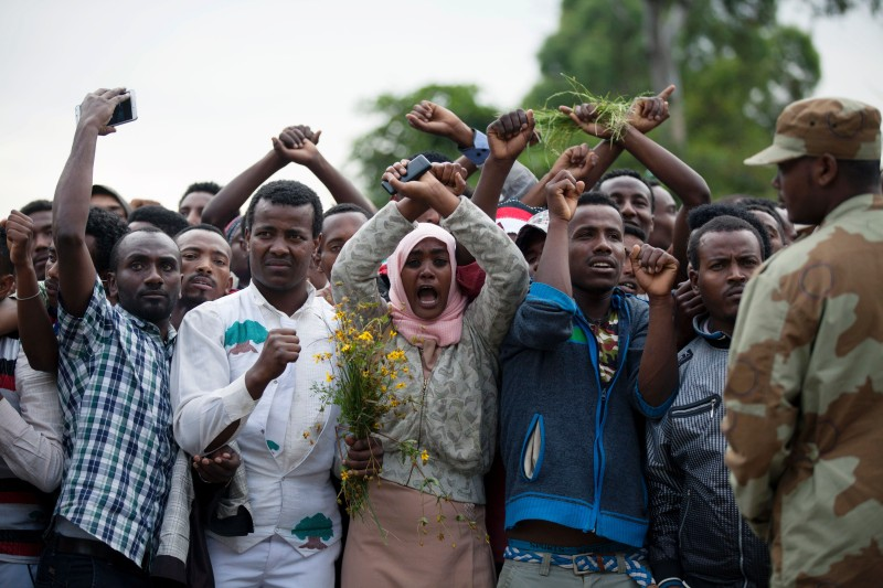 Residents of Bishoftu crossed their wrists above their heads as a symbol for the Oromo anti-government protesting movement during the Oromo new year holiday Irreechaa in Bishoftu on October 2, 2016. Several people were killed in a stampede near the Ethiopian capital on October 2 after police fired tear gas at protesters during a religious festival, according to an AFP photographer at the scene. Several thousand people had gathered at a sacred lake to take part in the Irreecha ceremony, in which the Oromo community marks the end of the rainy season, where participants crossed their wrists above their heads, a gesture that has become a symbol of Oromo anti-government protests. The event quickly degenerated, with protesters throwing stones and bottles and security forces responding with baton charges and then tear gas grenades. / AFP / Zacharias ABUBEKER        (Photo credit should read ZACHARIAS ABUBEKER/AFP/Getty Images)