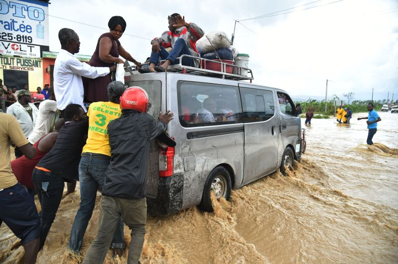 People try to cross the overflowing La Rouyonne river in the commune of Leogane, south of Port-au-Prince, October 5, 2016.  Haiti and the eastern tip of Cuba -- blasted by Matthew on October 4, 2016 -- began the messy and probably grim task of assessing the storm's toll. Matthew hit them as a Category Four hurricane but has since been downgraded to three, on a scale of five, by the US National Hurricane Center.  / AFP / HECTOR RETAMAL        (Photo credit should read HECTOR RETAMAL/AFP/Getty Images)