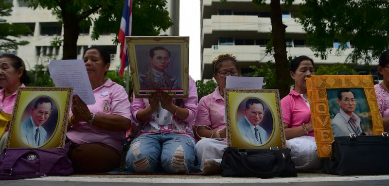 Women hold portraits of Thai King Bhumibol Adulyadej as they pray for his health at Siriraj Hospital, where the king is being treated, in Bangkok on October 12, 2016. Thailand's junta chief said he planned to hold talks with the Crown Prince following days of unprecedented concern over the health of ailing King Bhumibol Adulyadej. / AFP / MUNIR UZ ZAMAN        (Photo credit should read MUNIR UZ ZAMAN/AFP/Getty Images)