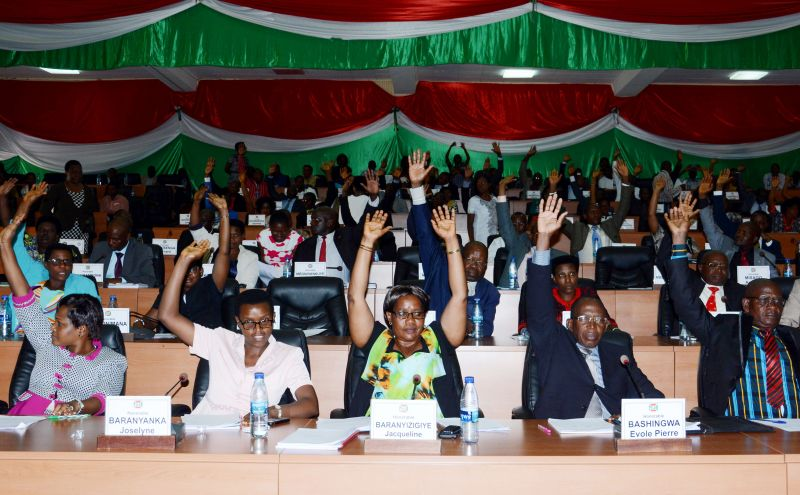 "Members of Burundi's National Assembly raise their arm to vote on October 12, 2016 in Bujumbura, for the withdrawal of the International Criminal Court (ICC) from the capital, after the UN began an enquiry into human rights abuses in the turbulent nation. The draft law was passed with 94 votes in favour, two against and 14 abstentions. It will next go to the Senate -- also dominated by the ruling party -- before being approved by President Pierre Nkurunziza. In April, ICC prosecutor Fatou Bensouda said she was conducting a ""preliminary examination"" of the situation in Burundi -- the first step towards a full investigation and possible prosecutions -- looking into allegations including murder, torture, rape and forced disappearances. / AFP / ONESPHORE NIBIGIRA        (Photo credit should read c)"